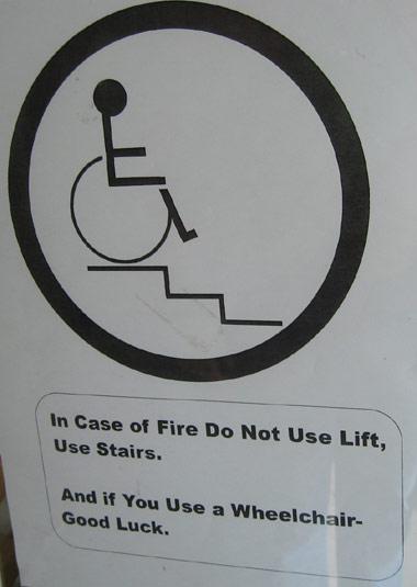 Das Bild zeigt ein Schild in der Stadt Oamaru (Neuseeland). Man sieht einen Rollstuhlfahrer vor Stiegen und darunter den Text: Im Falle eines Brandes nicht den Lift, sondern die Stiegen benützen. Wenn Sie einen Rollstuhl benützen - viel Glück.