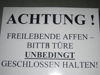 Das Bild zeigt ein Schild mit dem Text Achtung! Freilebende Affen -  bitte Türe unbedingt geschlossen halten! in Wien.