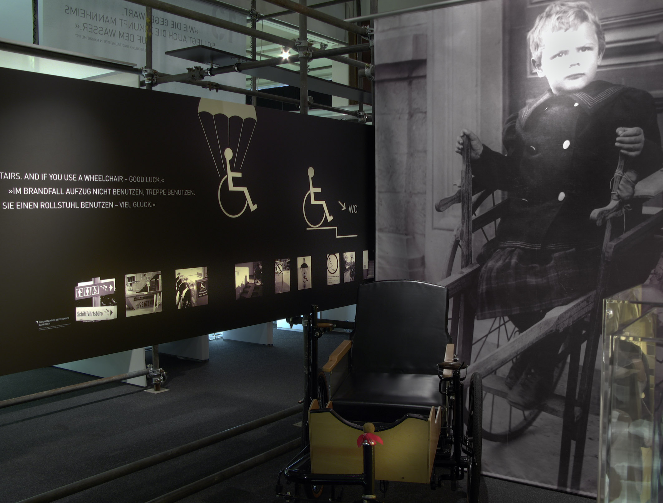 Man sieht eine Ausstellungswand mit Bildern der Woche von BIZEPS-INFO. Neben der Anstellungswand steht ein Rollstuhl.