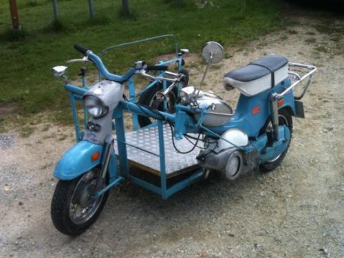 Man sieht ein Puch-Moped DS 50 so umgebaut, dass das Moped von einem  Rollstuhlfahrer im Rollstuhl gelenkt werden kann. Dafür wurde eine eigene Plattform (ehemaliger Beiwagen) geschaffen. Dieses Moped wurde in den 80er Jahren umgebaut.