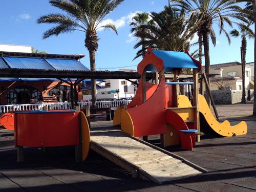 Man sieht ein kleines Klettergerüst auf einem Kinderspielplatz, welches mit einer Rampe teilweise barrierfrei erreichbar gemacht wurde.