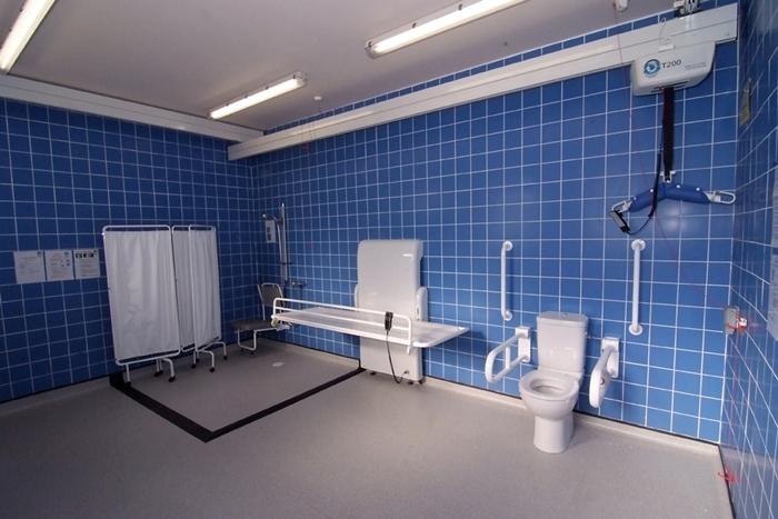 Man sieht einen der Changing Places aus Großbritannien. Das sind barrierefreie Toiletten, die zusätzlich zur Ausstattung einer barrierefreien Standard-Toilette über einen Deckenliftes und eine Liege verfügen. ({siehe Artikel https://www.bizeps.or.at/news.php?nr=15983})