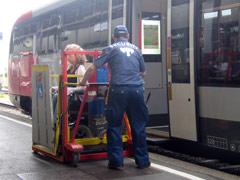Rollstuhlfahrerin wird mit einem Hebelift in den Zug gehoben