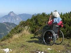 Rollstuhlfahrerin blickt vom Feuerkogel zum Traunstein