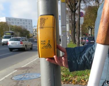 Blinde Frau drückt Rufknopf einer Akustikampel