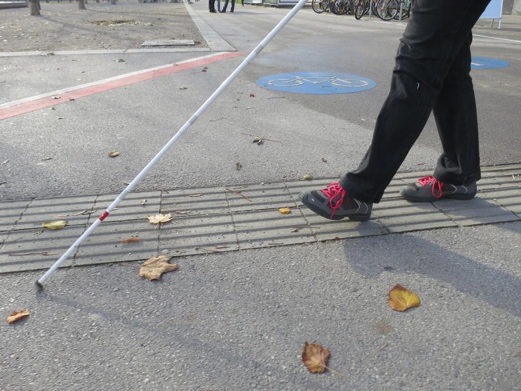 Blinde Frau geht Blindenleitlinien entlang