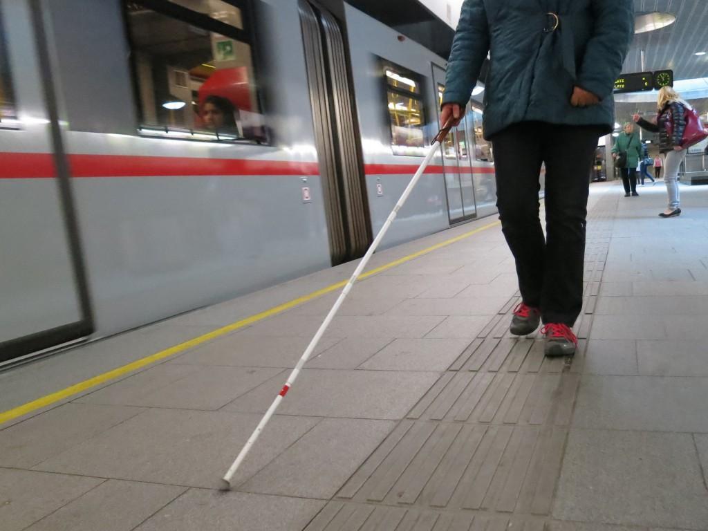 Blinde Frau mit Langstock in U-Bahn Station