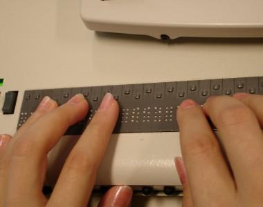 Finger auf einer Braille-Tastatur