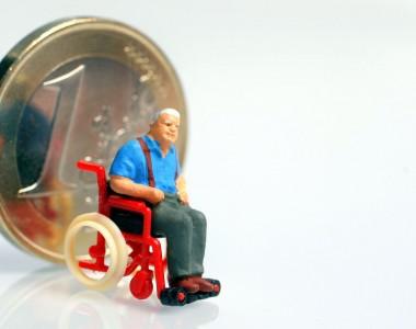 Rollstuhlfahrer vor einer Euromünze
