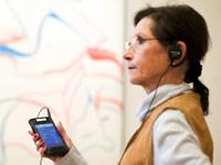 Frau mit multimedialer Ausstellungsguide