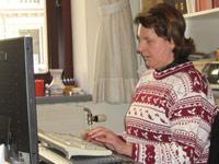 Eva Papst arbeitet am Computer mit einer Braillezeile