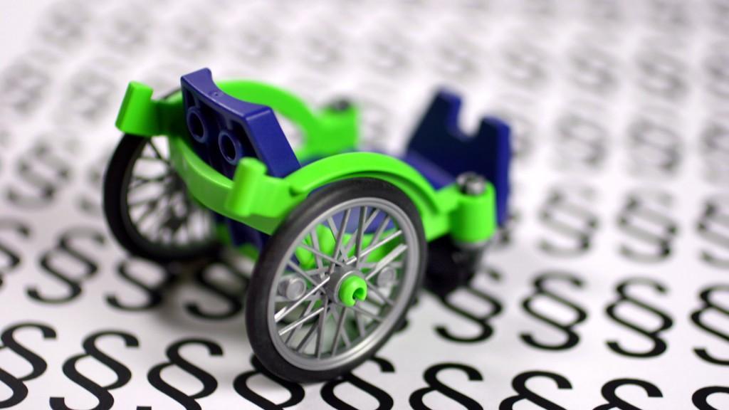 Rollstuhl vor Paragraphenzeichen