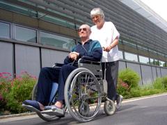 Frau schiebt Mann im Rollstuhl