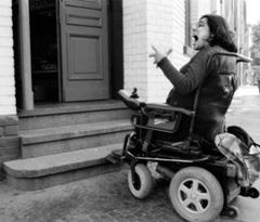 Frau im Rollstuhl vor Stufen. Sie schreit