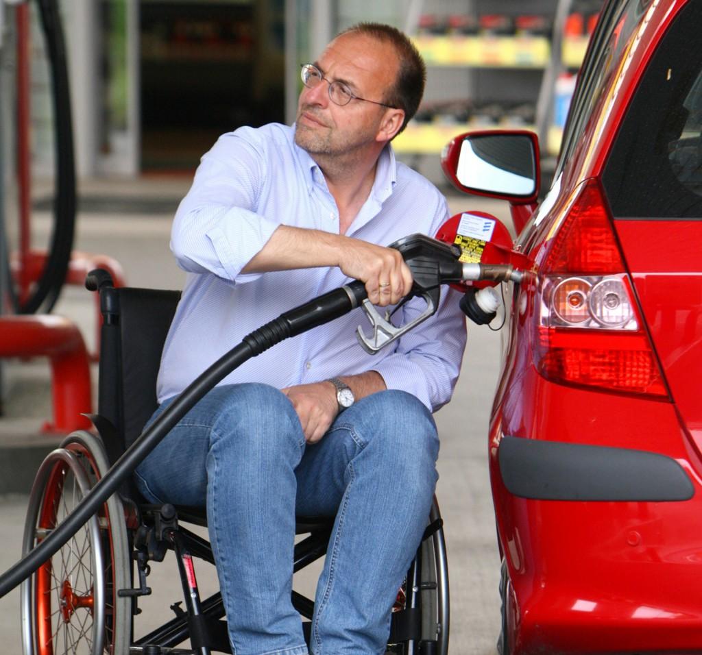Rollstuhlfahrer tankt sein Fahrzeug