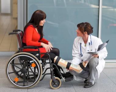 Eine Frau im Rollstuhl mit Gipsbein wird von einer Ärztin begutachtet.