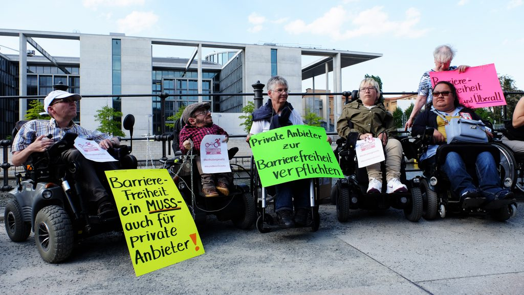 Gruppe von Rollstuhlfahrern demonstriert