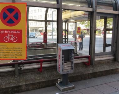 Außenbereich U1 Station Nestroyplatz. Ausgabebox für Zeitung Österreich verstellt den Handlauf direkt neben einem Schild auf dem steht, dass Fahrradabstellen verboten ist für das sichere Vorankommen von Menschen mit Behinderungen.