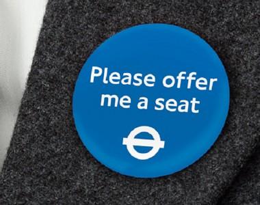 Blauer Ansteckbutton mit weißer Schrift: Please offer me a seat