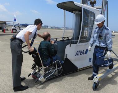 Rollstuhlfahrer in Japan wird in einen Hebelift für kleine Flugzeuge geschoben der kaum breiter als der Bordrollstuhl ist.