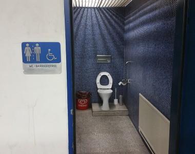 Ein barrierefreies WC das auf einem erhöhten Podest steht. Außen an der Wand steht WC-BARRIEREFREI