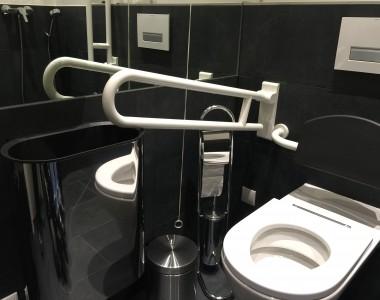 Man sieht ein WC Muschel und daneben der Haltegriff zum klappen. Der Griff kann allerdings nicht ganz runtergeklappt werden weil der Mistkübel im Weg ist. Der Griff ist nicht benützbar.