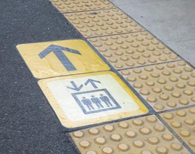 Ein taktiles Blindenleitsystem. Daneben klebt am Boden ein Aufzugsymbol mit einem Wegweiser wo er zu finden ist.