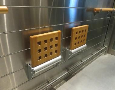 Das Innere eines Aufzuges. Man sieht zwei Klappsitze aus Holz die nach unten geklappt werden können.