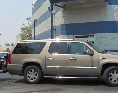 Ein Auto, Cadillac Escalade, ist von der Seite zu sehen. Am Heck des Autos ist ein Elektrorollstuhl auf einem Hublift fixiert.