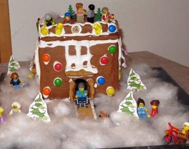 Ein Lebkuchenhaus mit eine Rampe die auf einen schneebedeckten Platz führt. Die Bewohner sind Legofiguren. Auch am Dach sieht man Bewohner.