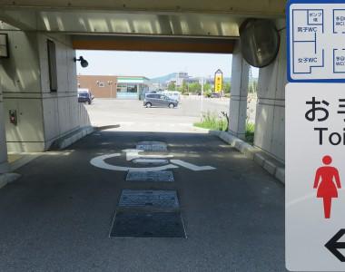 Ein überdachter Behindertenparkplatz direkt neben einer barrierefreien Toilette. Ein Schild erklärt, dass man als behinderter Mensch direkt neben der Toilette parken darf.