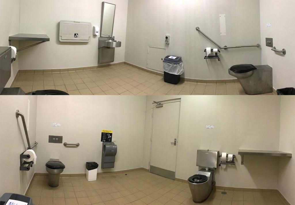 Ein Panoramabild eines barrierefreien WCs. Es gibt eine Toilette in der Ecke mit Haltegriffen, eine Toilette die von beiden Seiten anfahrbar ist, ein unterfahrbares Waschbecken, einen Wickeltisch und Händetrockner. Der Raum ist ca. 10 Quadratmeter groß.