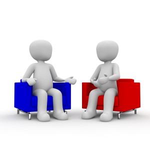 2 gesichtlose Figuren sitzen auf einem roten und blauen Sessel und diskutieren.