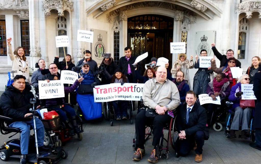 Doug Paulley im Vordergrund mit seinem Anwalt dahinter Aktivisten mit Transport for All und Campaign win Schildern.