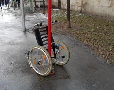 Ein Rollstuhl ist bei einer Straßenbahnhaltestelle an einen Mast angekettet. Es fehlen schon die Vorderräder.