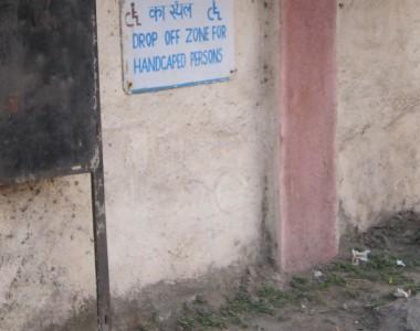 Eine Hauswand mit Schild,davor ein Erdboden. Auf dem Schild steht DROP OFF ZONE FOR HANDCAPED PERSONS