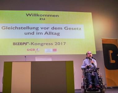 Markus Ladstätter hält Eröffnungsrede beim BIZEPS-Kongress 2017 am Podium vor einer Willkommensfolie.