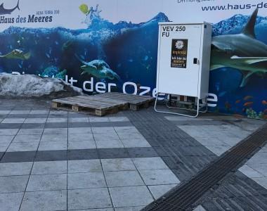Am Vorplatz des Hauptbahnhof Wiens führt ein taktiles Leitsystem in ein Baustellenholzwand. Außerdem stehen 2 Europlatten darauf. Rechts an der Wand steht noch eine Metallbox und links ein großer Schneehaufen.