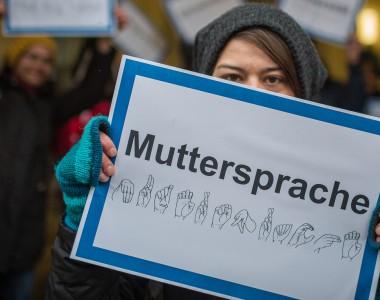 Frau hält Schild mit Aufschrift: Muttersprache