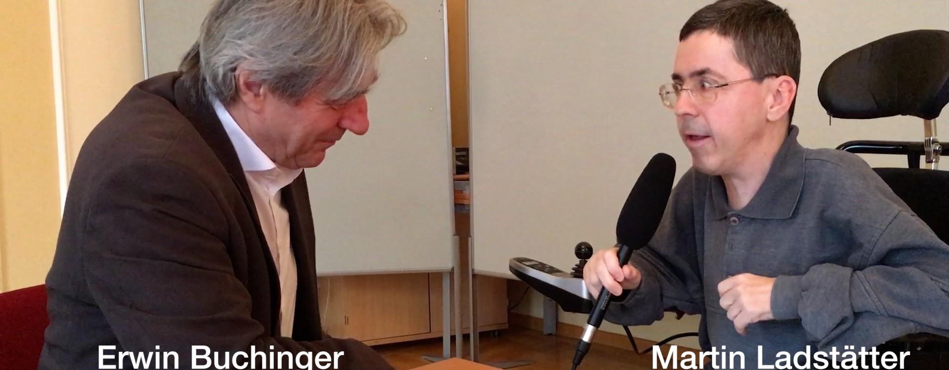 Erwin Buchinger wird von Martin Ladstätter interviewt. Sie sitzen bei einem Tisch. Martin Ladstätter hält ein Mikrofon.