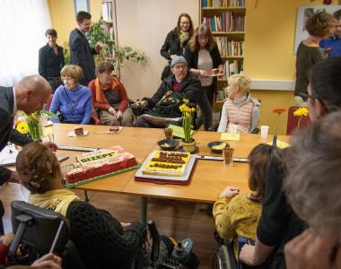 Viele Menschen in unserem großen Zimmer rund um die Torte 25 Jahre Peer Beratung
