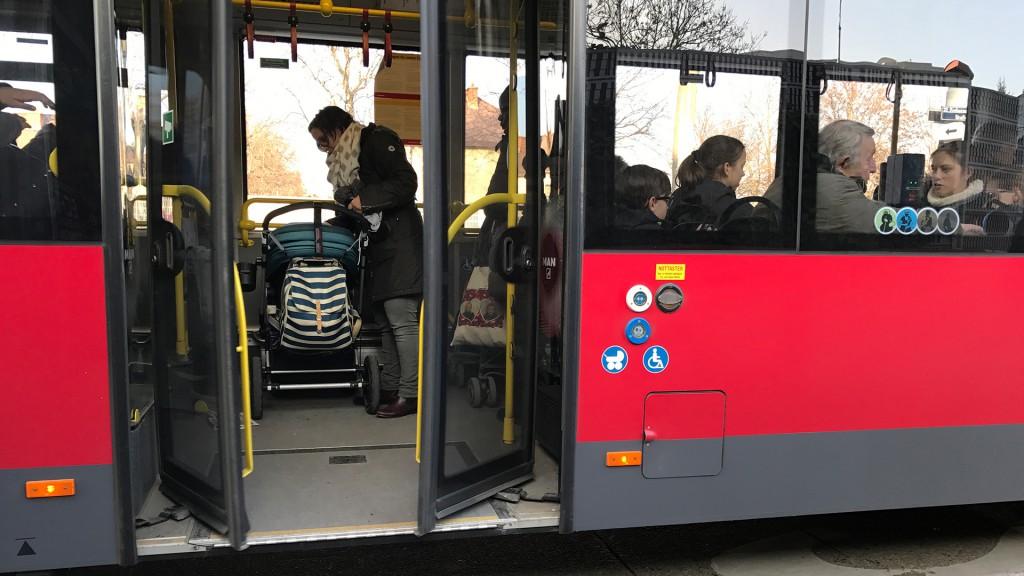 Ein Bus der Wiener Linien. Man sieht hinein, 2 Kinderwägen stehen auf dem Rollstuhl- und dem Kinderwagenplatz. Die Tür schließt gerade.