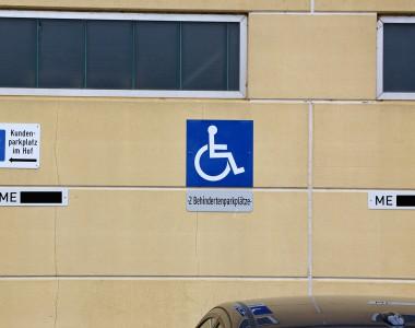 Eine Hausmauer. In der Mitten ein Schild 2 Behindertenparkplätze. Rechts und links davon sind aber für Mitarbeiter genau diese Parkplätze mit Nummerntafel reserviert. Ein weiteres Schild zeigt nach links und sagt Kundenparkplätze im Hof.