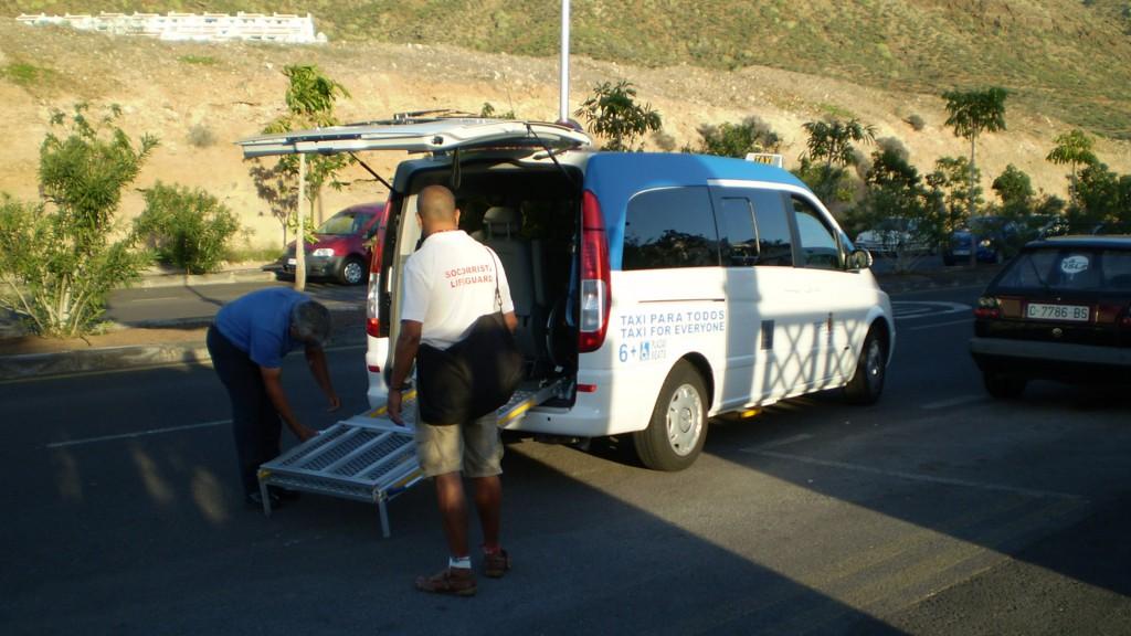 Palmen im Hintergrund. Im Vorderground ein Großes Taxi bei dem hinten eine Rampe ausgeklappt wird. Auf der Seite des Autos steht Taxi para todos - Taxi for everyone