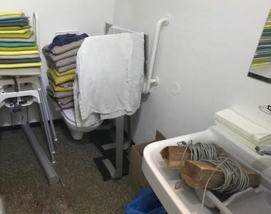 Barrierefreies WC vollgeräumt mit 2 Tischen, Kindersitzen, Feuerholz im Waschbecken und vielen vielen Pölstern. Das WC sieht man kaum.