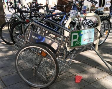 An einem Fahrrradständer ist ein Fahrradanhänger abgestellt, der eine Mischung aus Rollstuhlrädern und Armstützen, Einkaufswagenkorb und einer Stange ist.