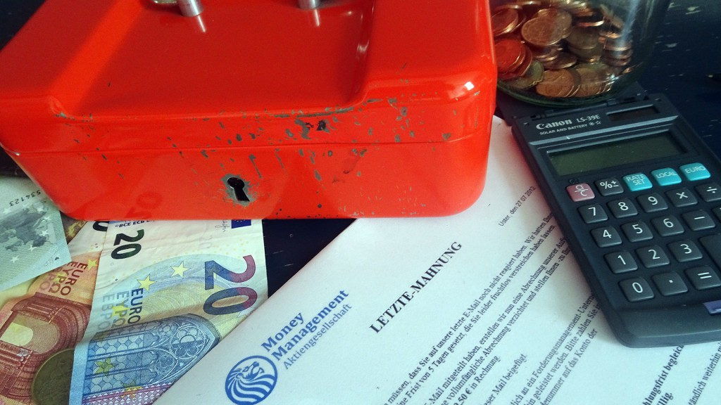 Geld, Taschenrechner und Handkassa vor Letzter Mahnung