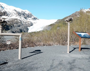 2 Ferngläser zeigen auf einen Gletscher. Das Linke ist unterfahrbar für Rollstühle