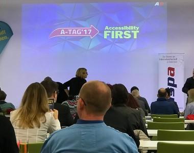 Begrüßungspräsentation mit Titel A-Tag 17 Accessibility First. Davor sitzend einige Besucherinnen der Veranstaltung.