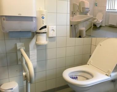 Bild in Bild, groß sieht man eine Nahaufnahme einer barrierfreien Toilette die keine seitlichen Haltegriffe hat aber davor einen der im Weg ist.